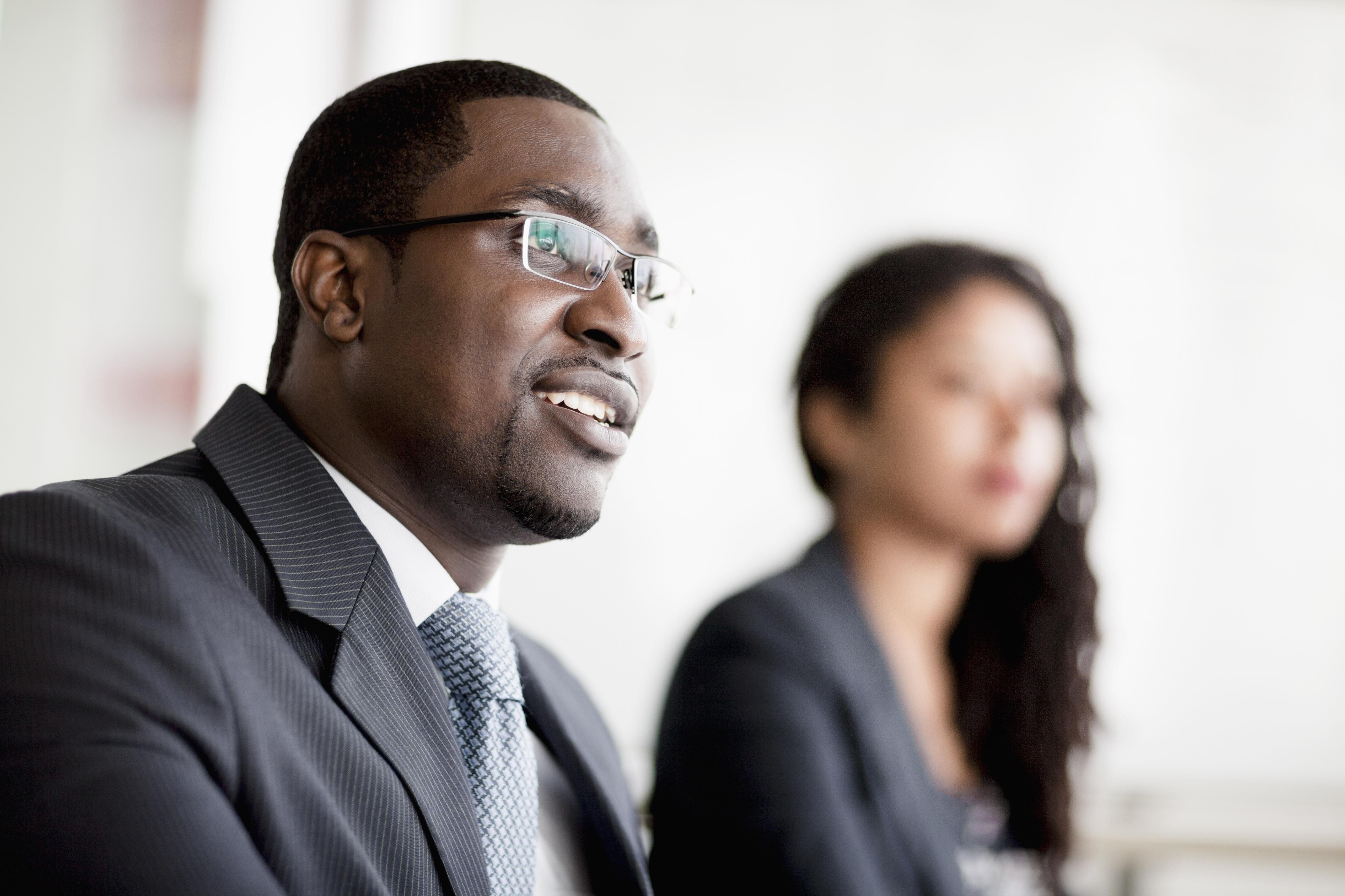 smiling-businessman-listening-at-a-business-PJW9URS.jpg